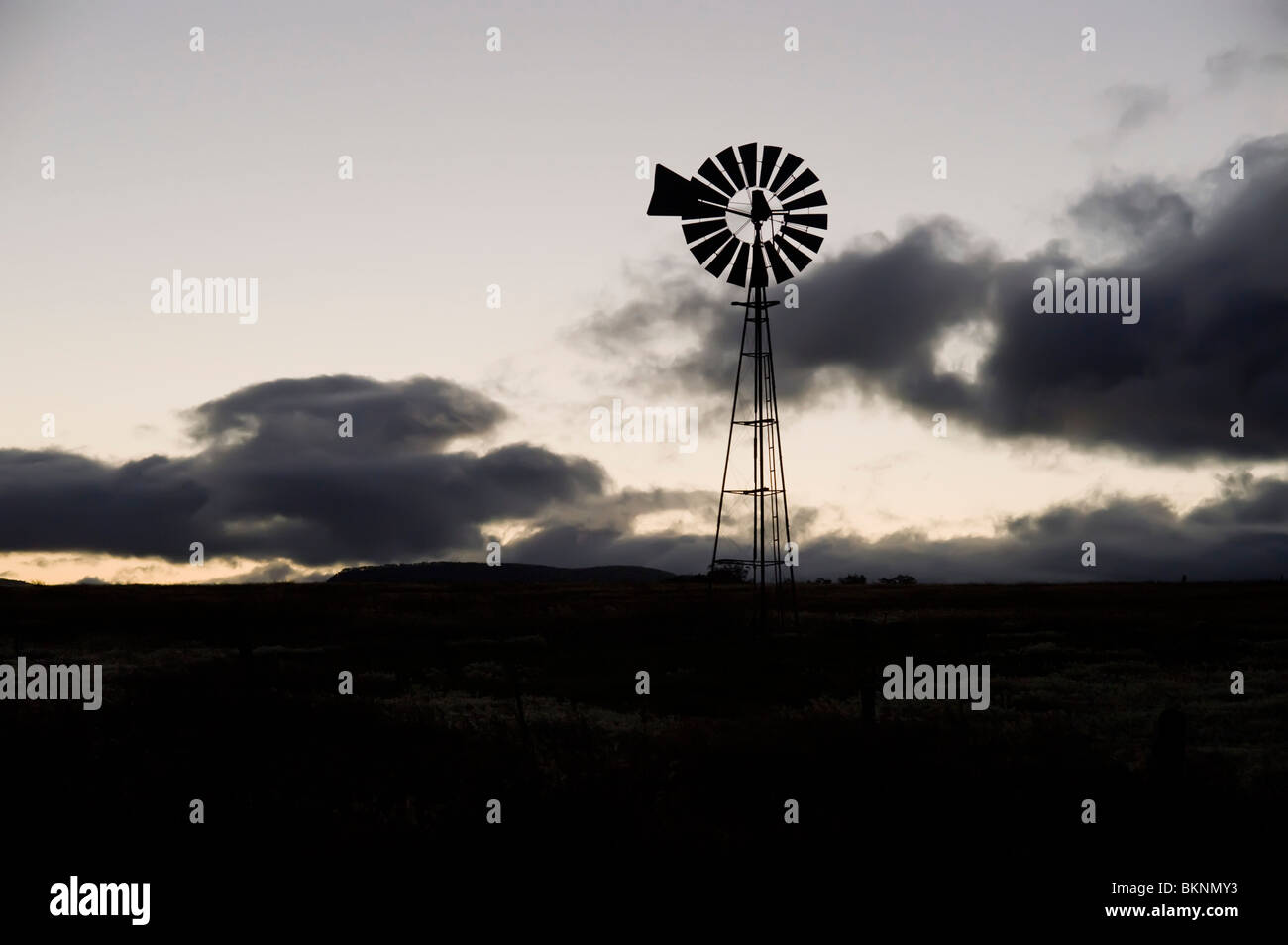 Windmill silhouetted against clouds Stock Photo