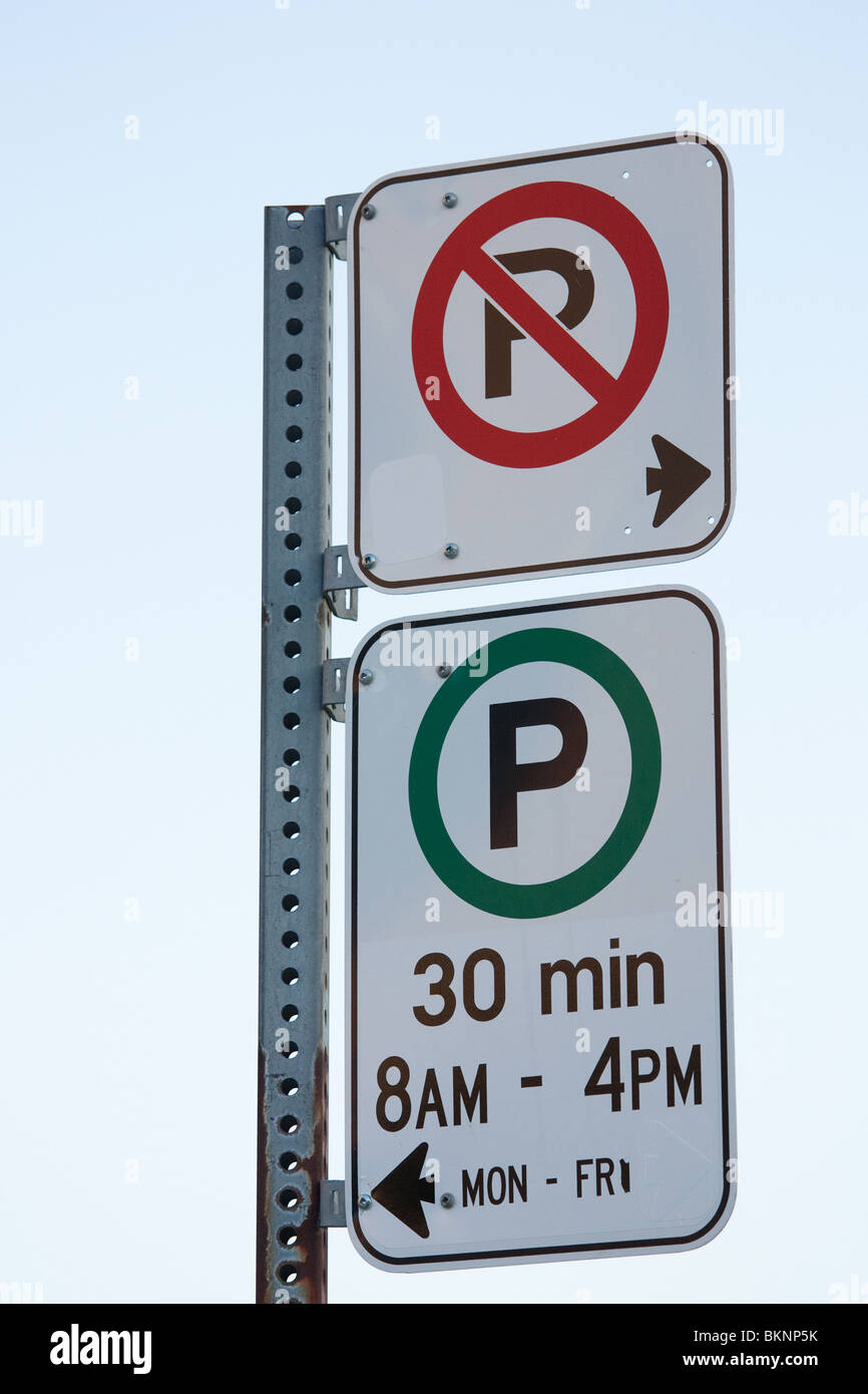 no parking sign left parking 30 min limit right - Stock Image