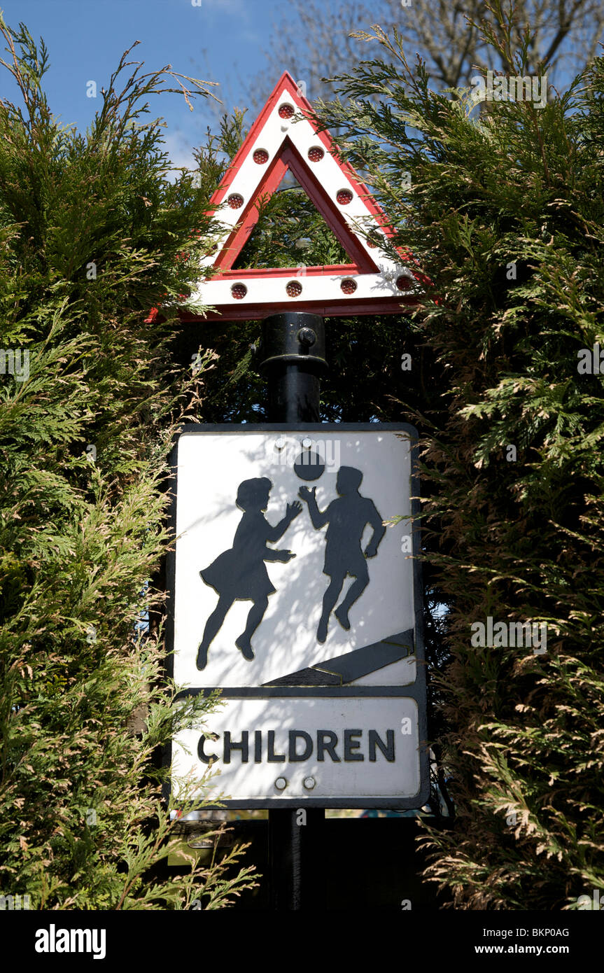 An old highways roadside triangular reflective warning sign showing two children playing with a ball - Stock Image