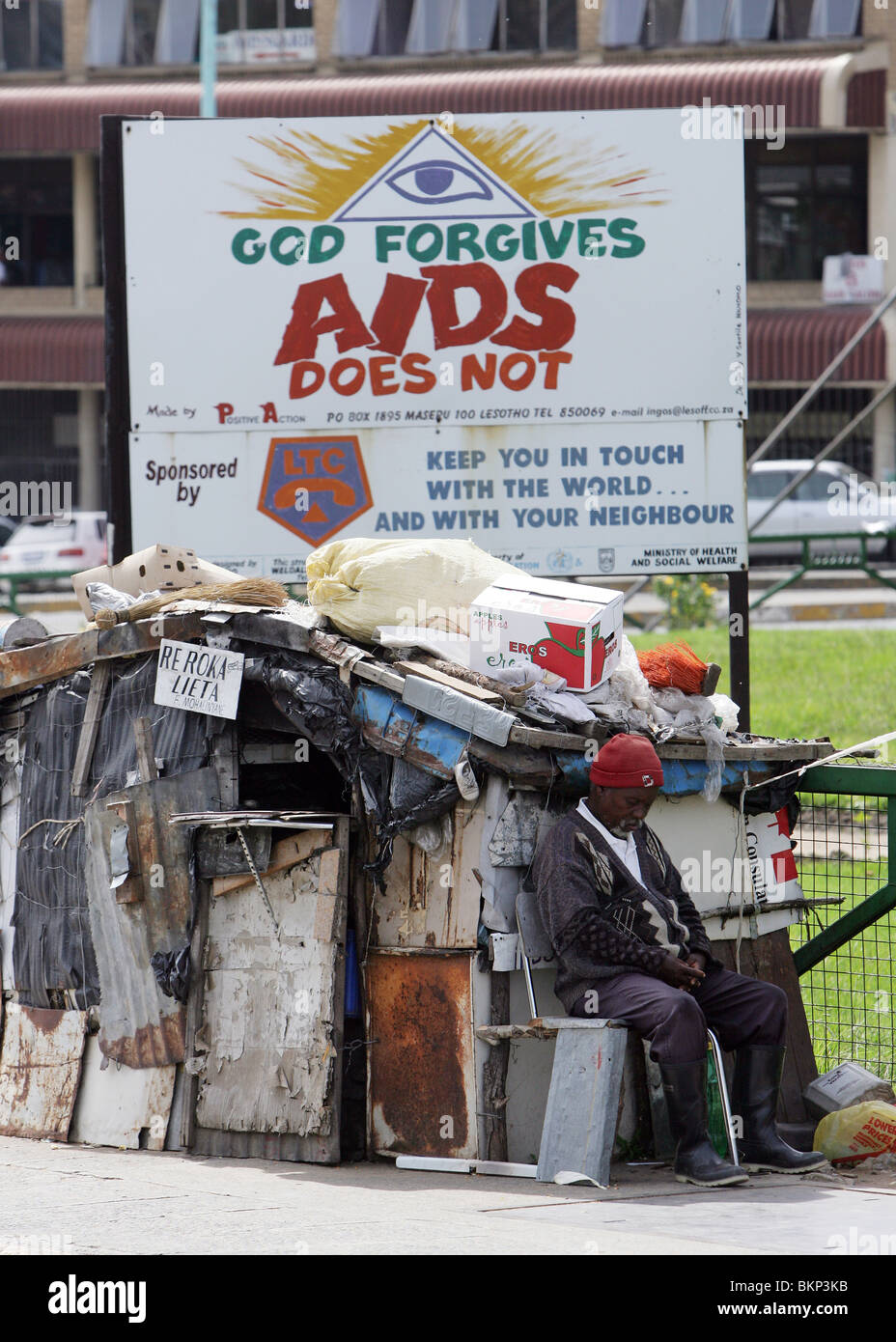 man sitting under a roadside bilboard warning of the dangers of HIV Aids. Maseru, capital of Lesotho - Stock Image
