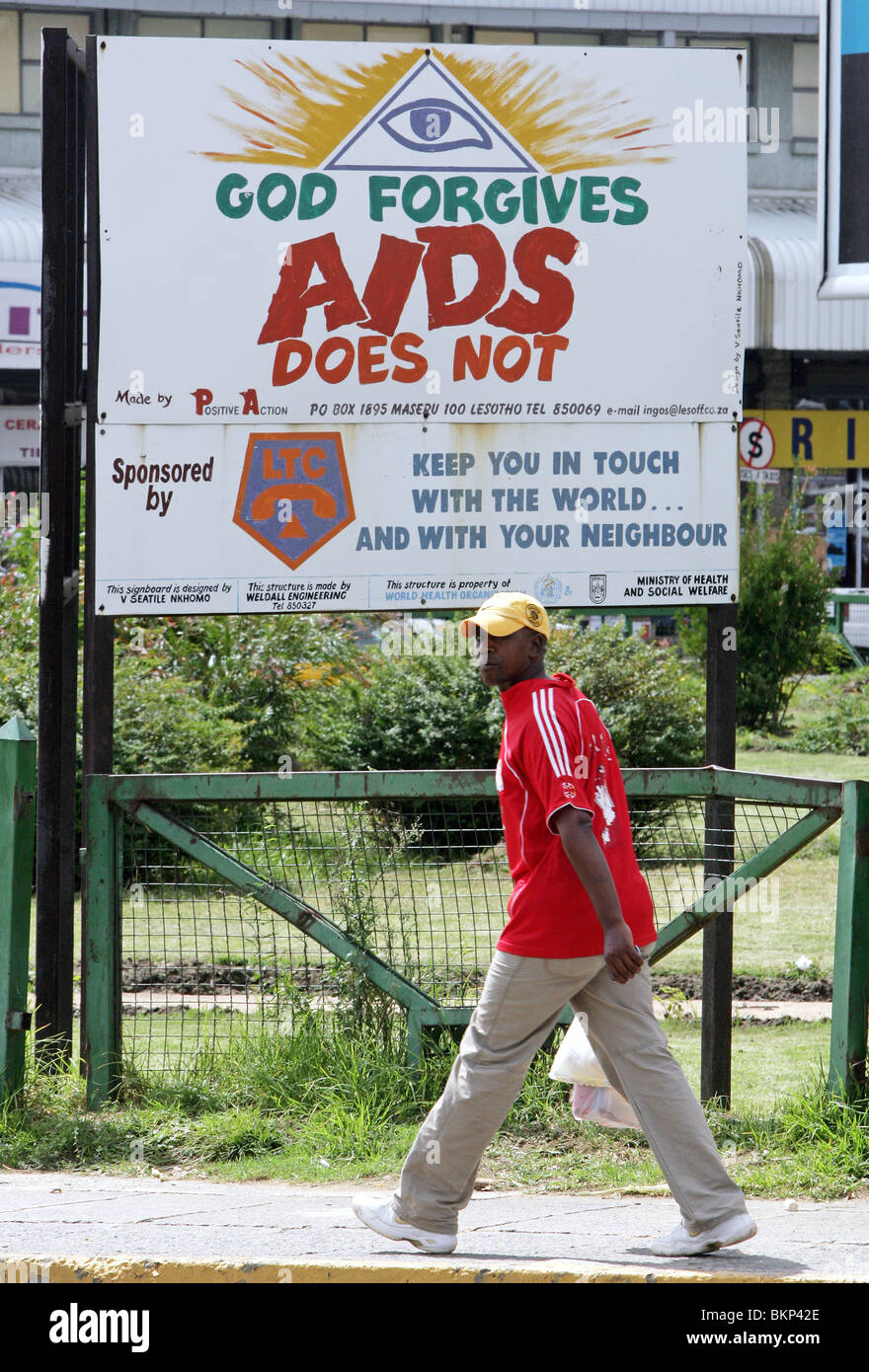 a man passes a roadside hoaring warning of the dangers of HIV Aids. Maseru, capital of Lesotho - Stock Image