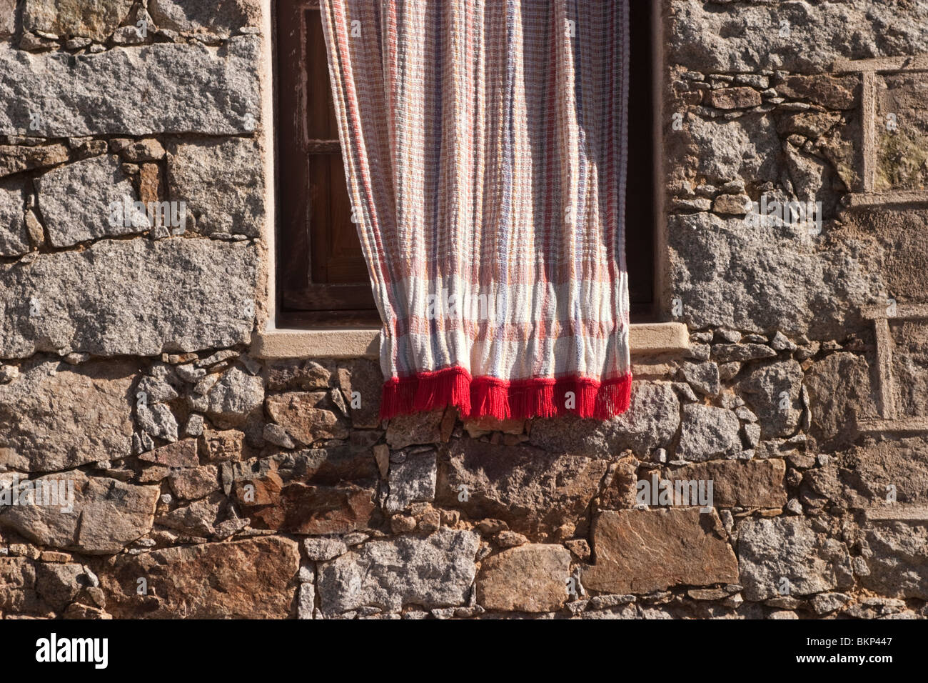 Curtain over window in stone built house Corsica - Stock Image