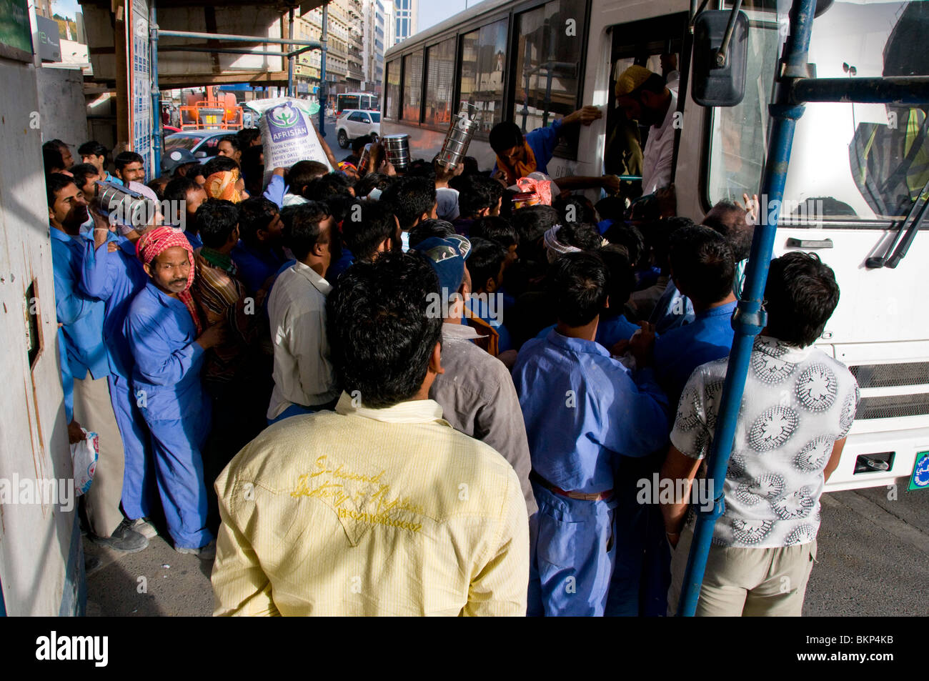 Foreign  workers taking bus Dubai - Stock Image