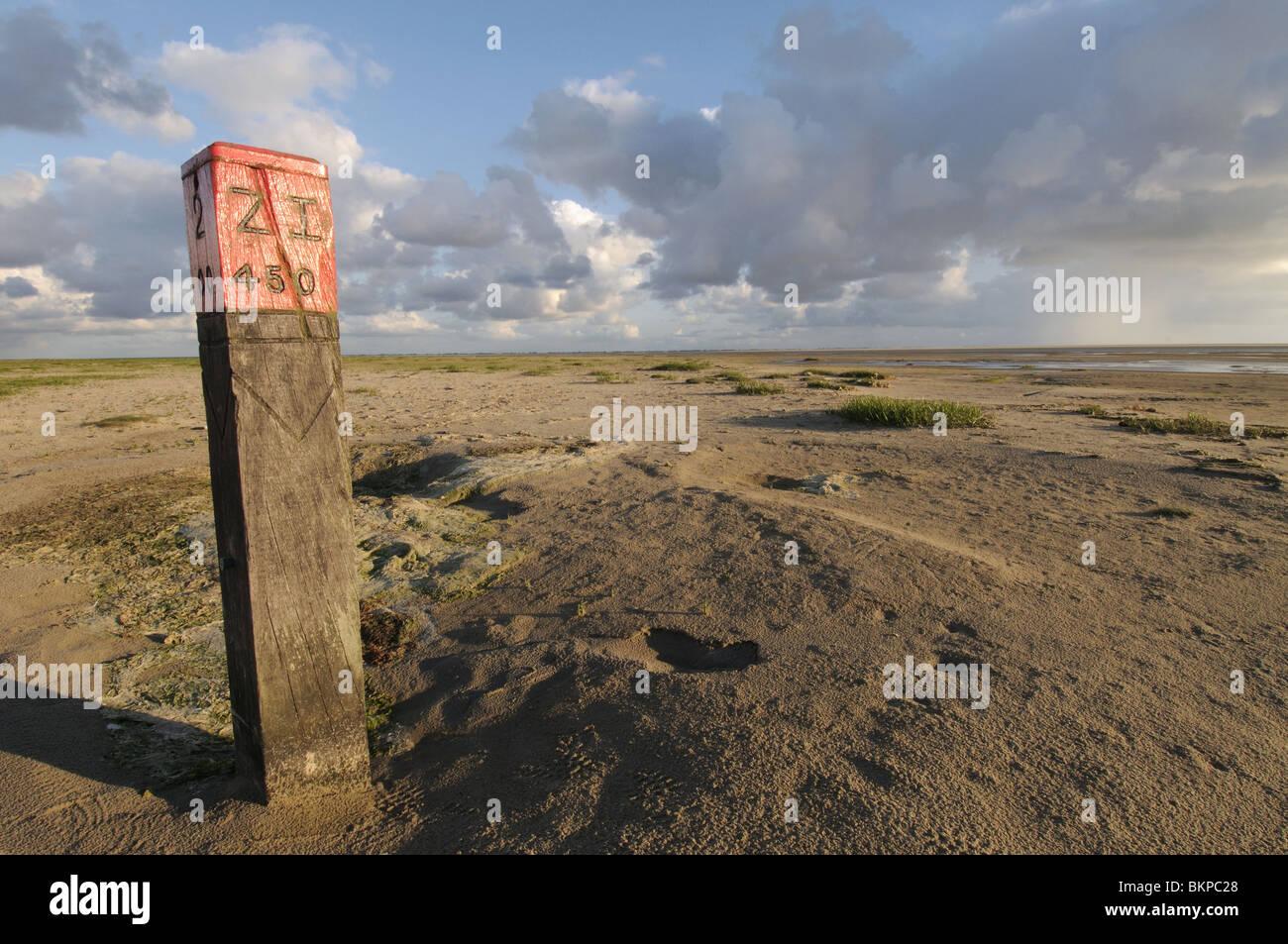 Strandpaal op grote, open en verlaten strandvlakte; Wooden pole on deserted beach Stock Photo