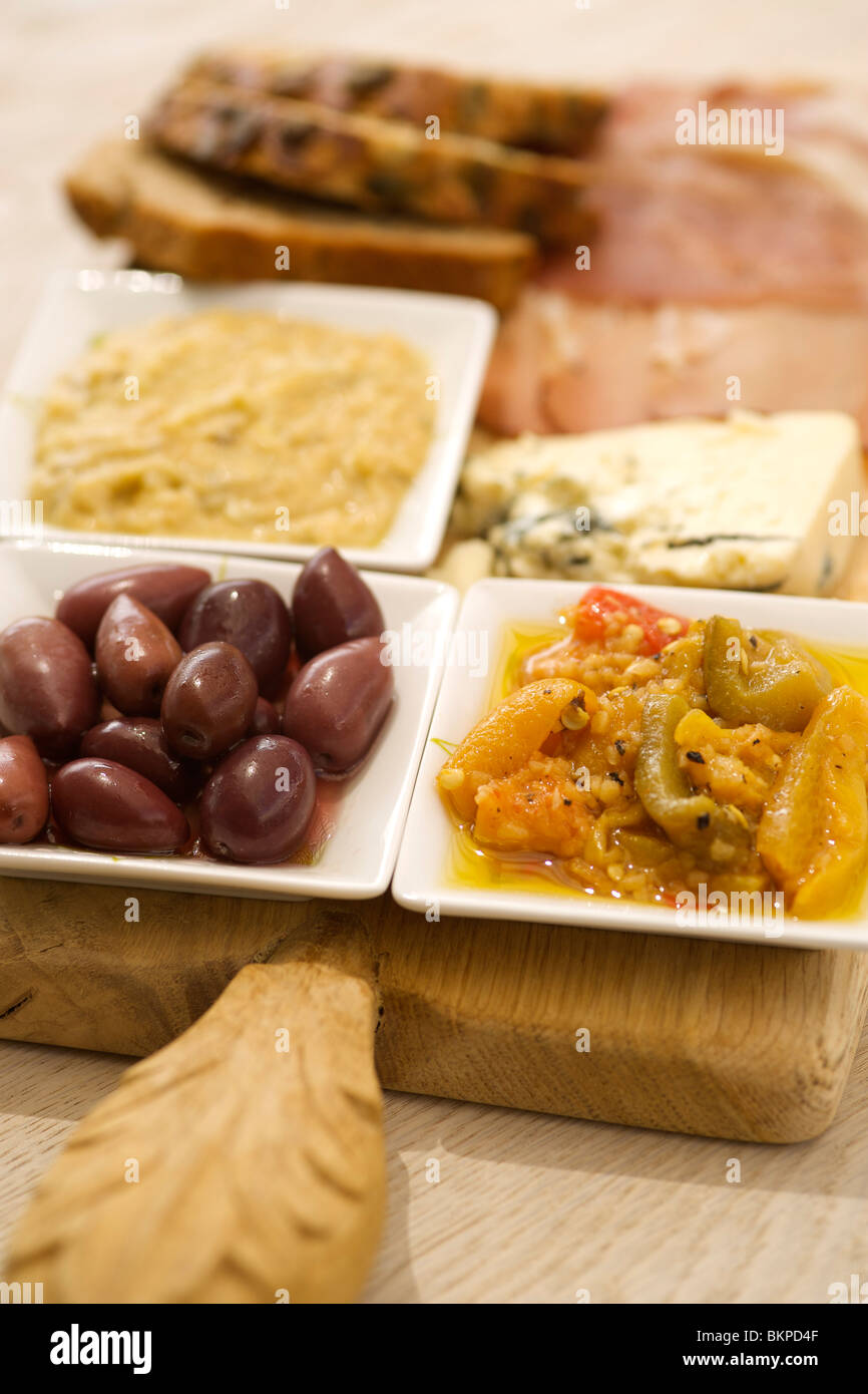 Platter of snacks including kalamata olives, humus, blue cheese, peppers and sunflower seed bread. - Stock Image