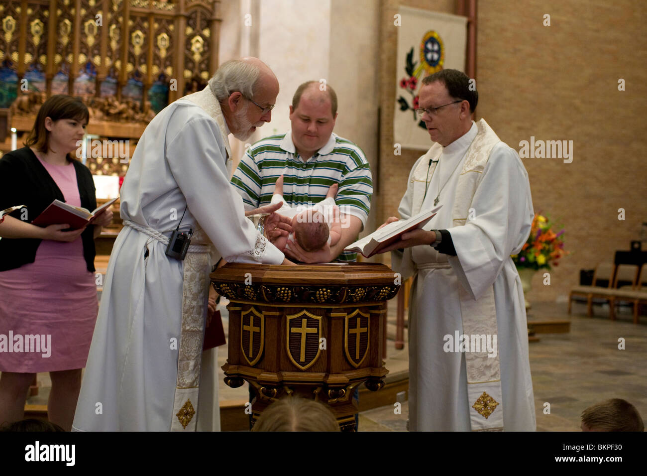 Pastors baptize infant girl in baptismal font as her father holds her and her mother watches on alter at Lutheran - Stock Image