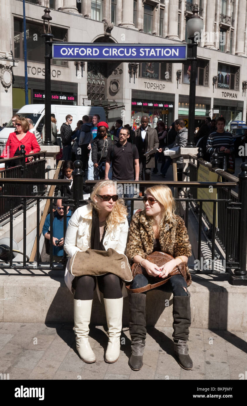 Two girls sitting at Oxford Circus, entrance to Underground Station,London UK - Stock Image
