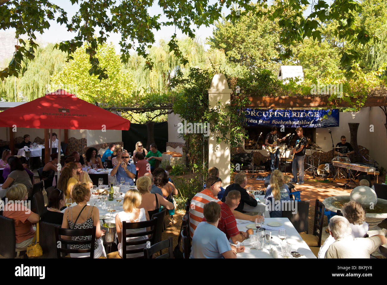People eating lunch and watching live music at the Allora restaurant in Franschhoek. - Stock Image
