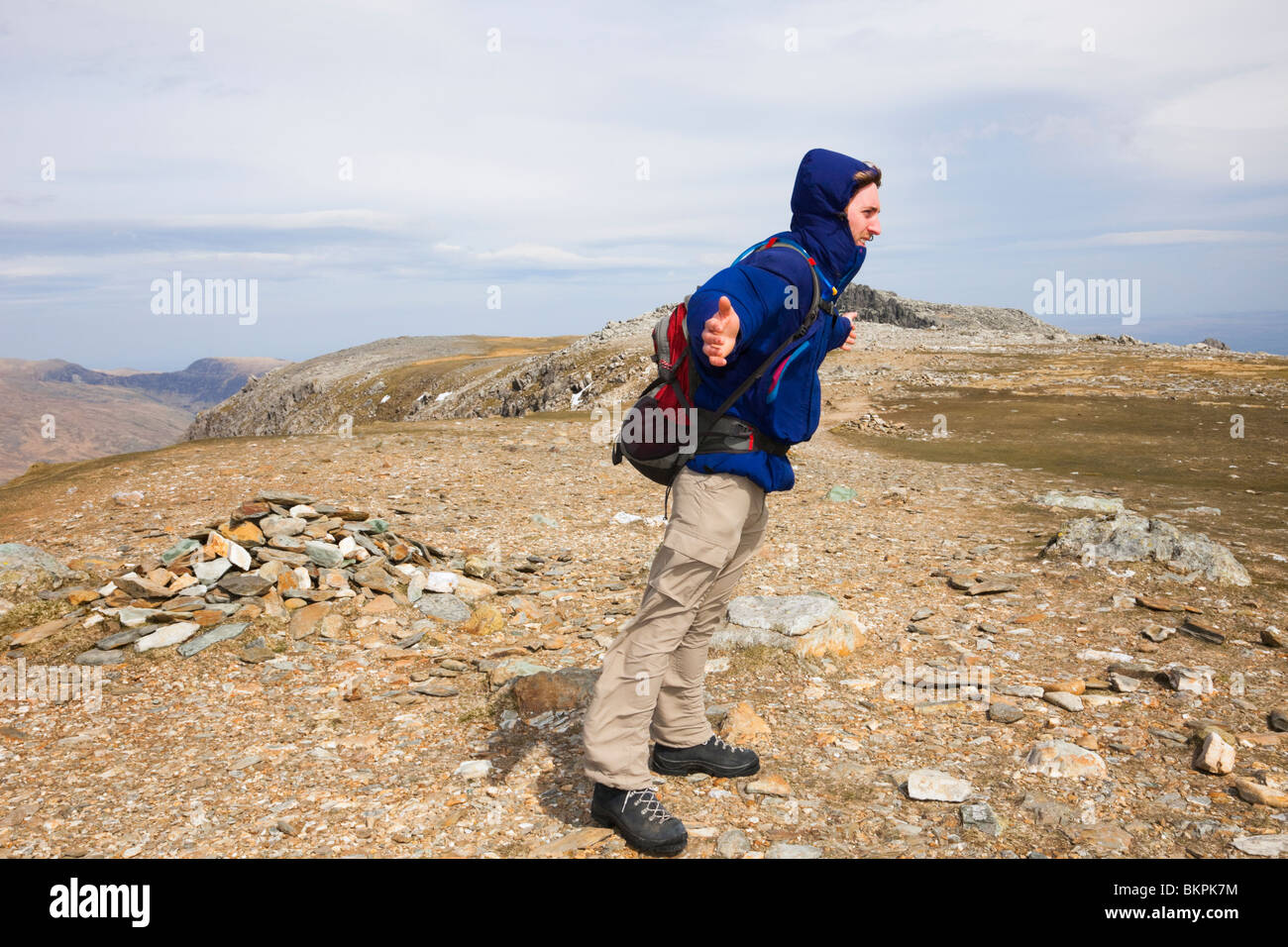 Man leaning in to the wind on a very windy day on exposed mountain top of Glyder Fawr in Snowdonia National Park - Stock Image