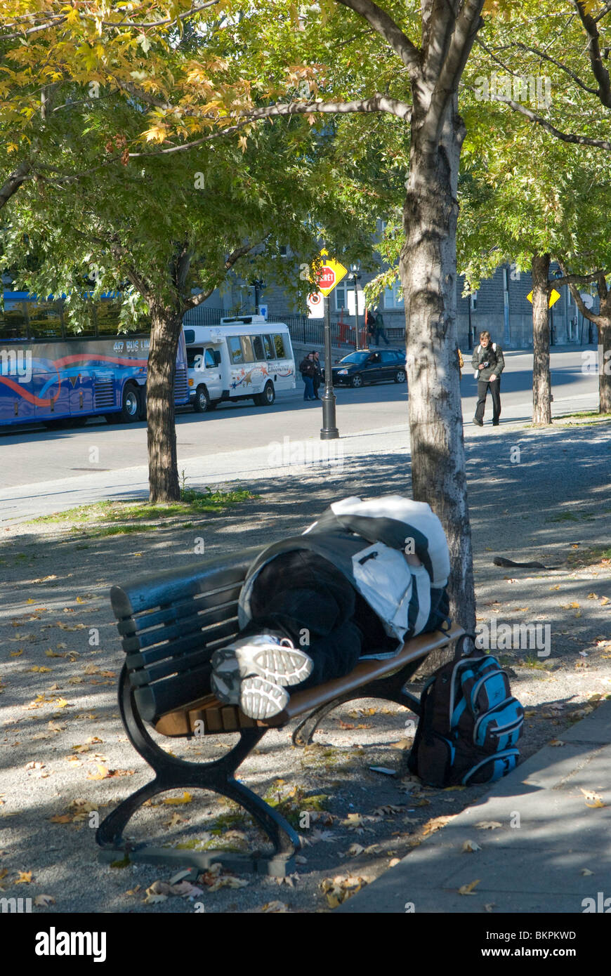 Homeless person sleeping on a bench Montreal Canada - Stock Image
