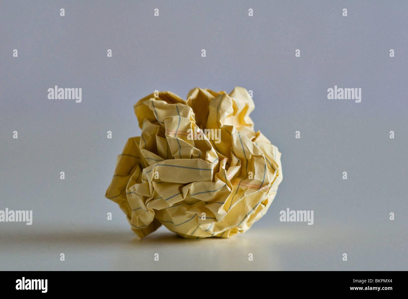 Crumpled yellow paper ball. - Stock Image