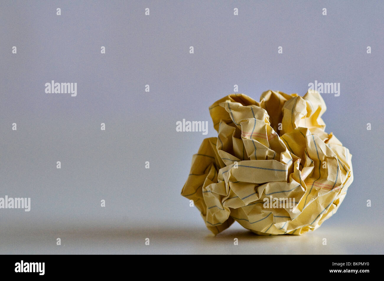 Crumpled yellow paper ball of failed ideas. - Stock Image