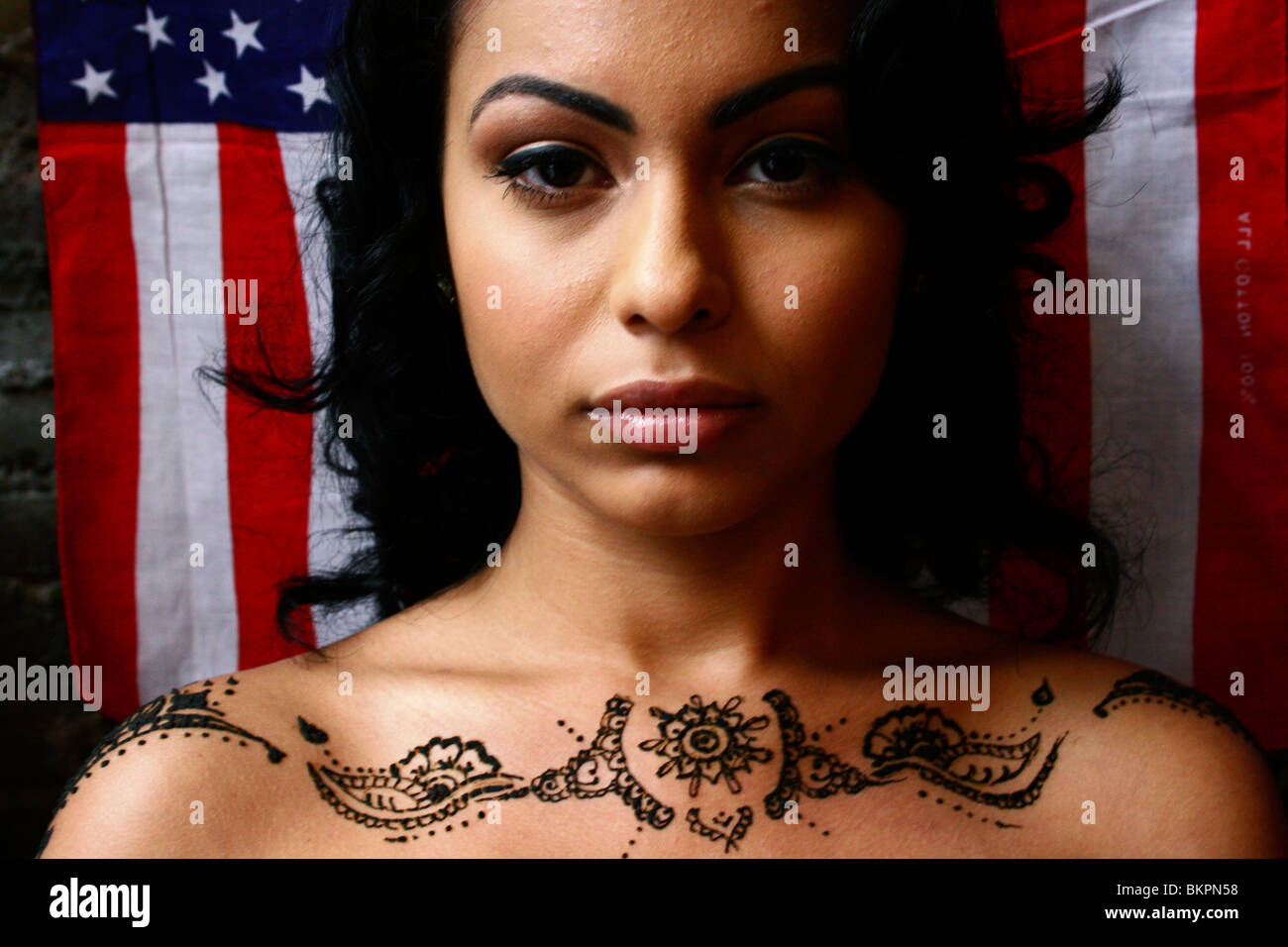 Close up portrait of woman with henna body art on her shoulders, and the American flag as the background. - Stock Image