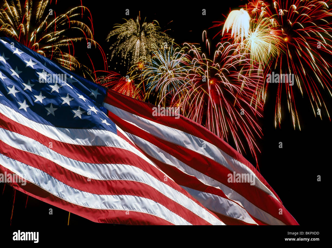 united states flag waving in front of fireworks display patriotic composite stock image
