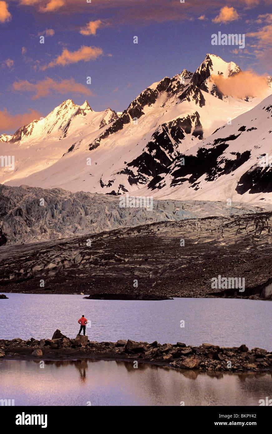 Male Hiker enjoys the view in front of Walker Glacier, Glacier bay National Park, Southeast, Alaska - Stock Image