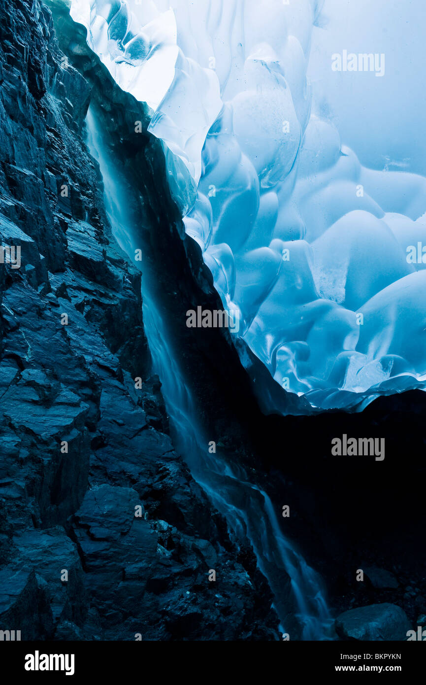 A waterfall trickles its way down the rock face of an ice cave inside the Mendenhall Glacier, Juneau, AK. Summer. - Stock Image