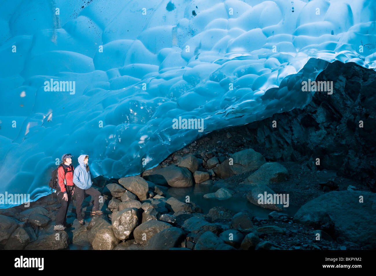 Mother and daughter hikers explore an ice cave on the inside of the Mendenhall Glacier, Juneau, Alaska - Stock Image