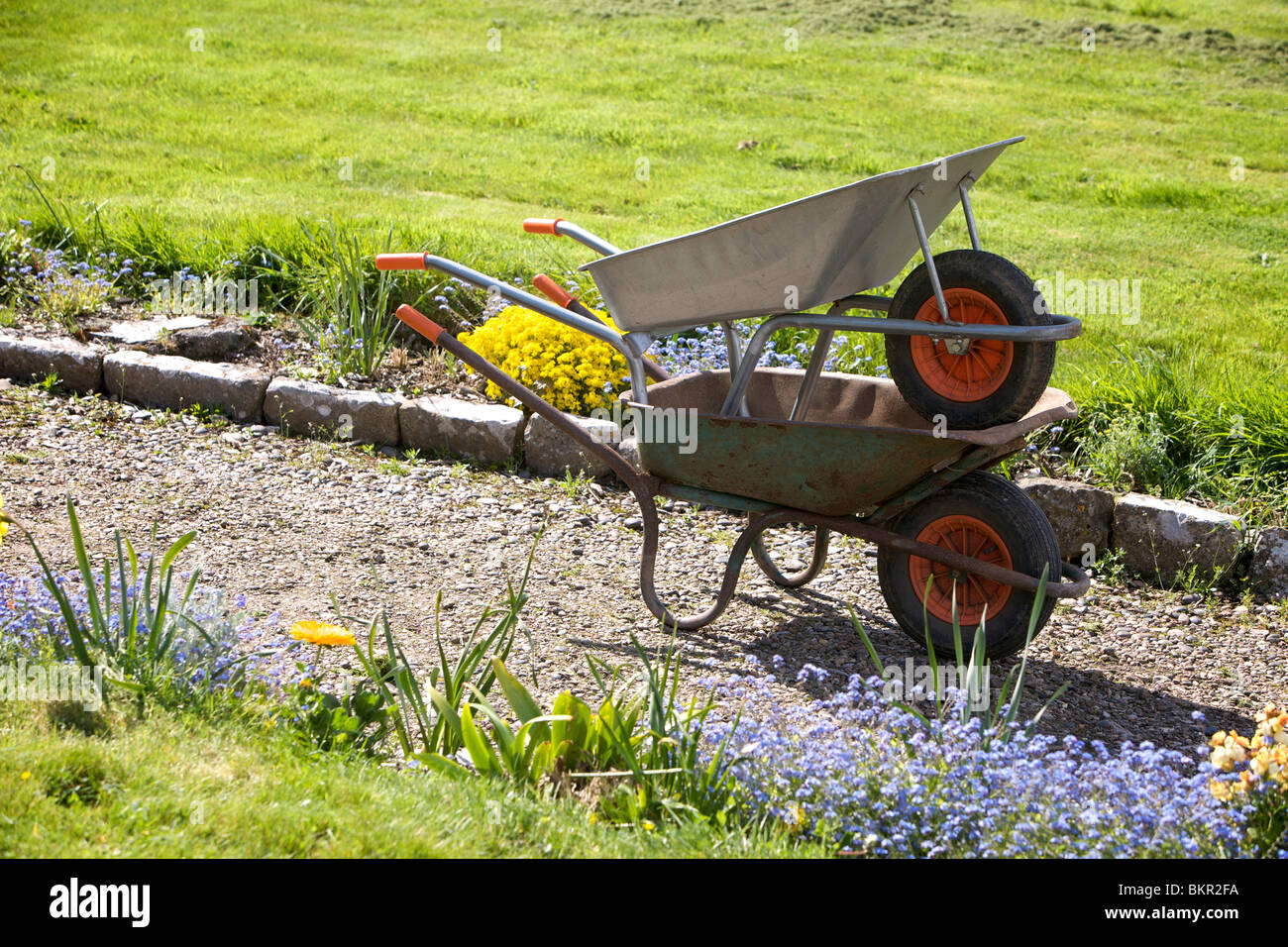 Wheelbarrows stacked in an English country garden - Stock Image