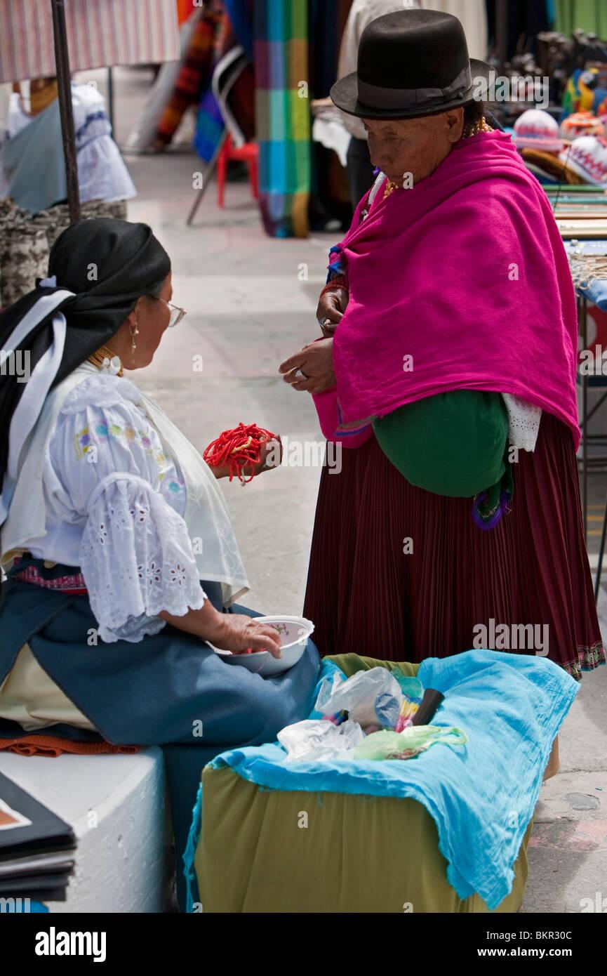 Ecuador, Two women negotiate the price of beads at Otavalo Indian Market. - Stock Image