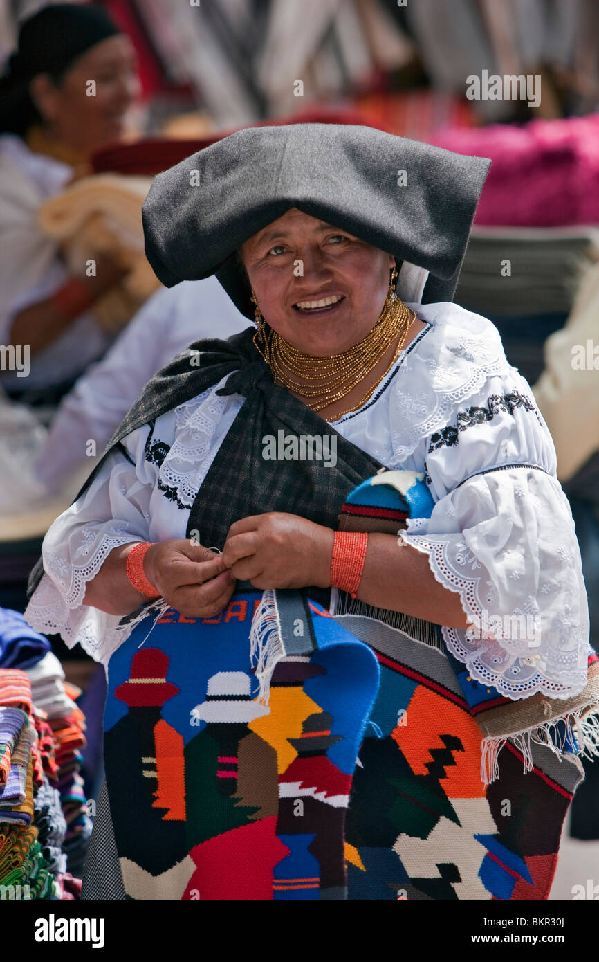 Ecuador, An indigenous Ecuadorian woman puts the final touches on her small woollen wall hangings at Otavalo market. - Stock Image