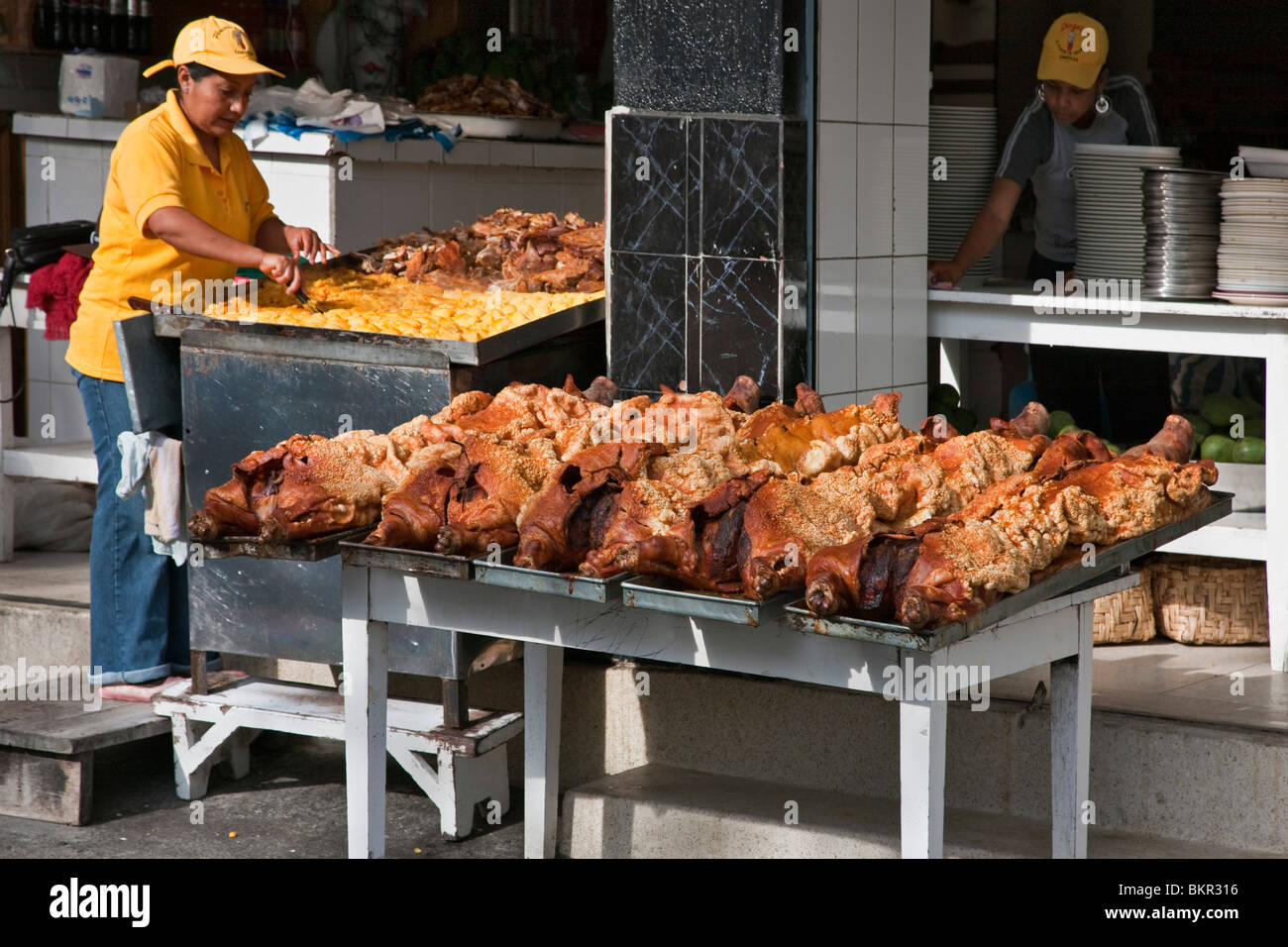 Ecuador, Roast suckling pigs on display at an open-air foodstall at Sangolqui market. - Stock Image