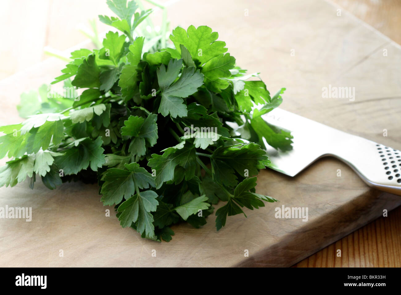 Parsley on chopping board - Stock Image