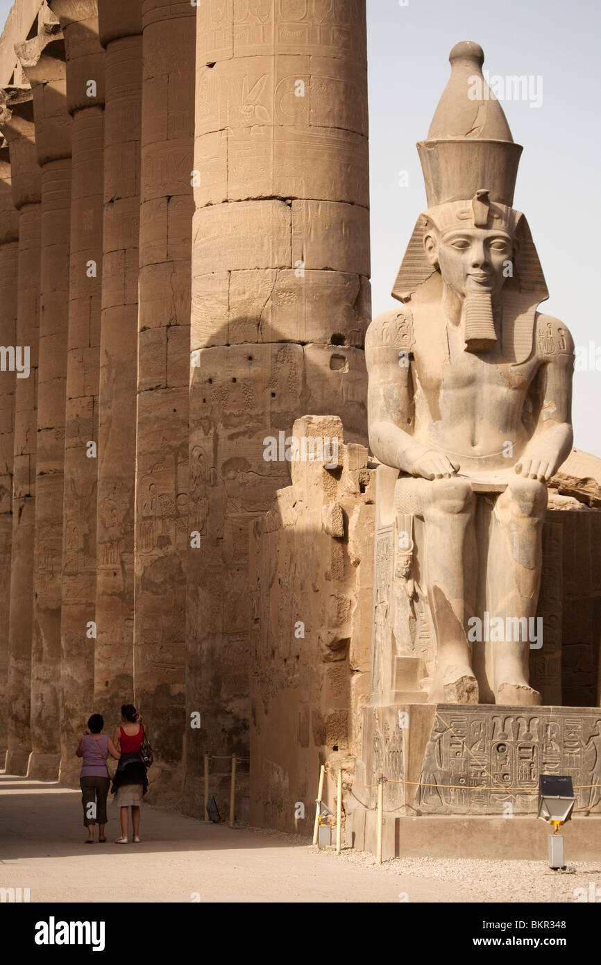 Egypt, Luxor. A pair of tourists wander down the avenue of massive columns at Luxor Temple. - Stock Image