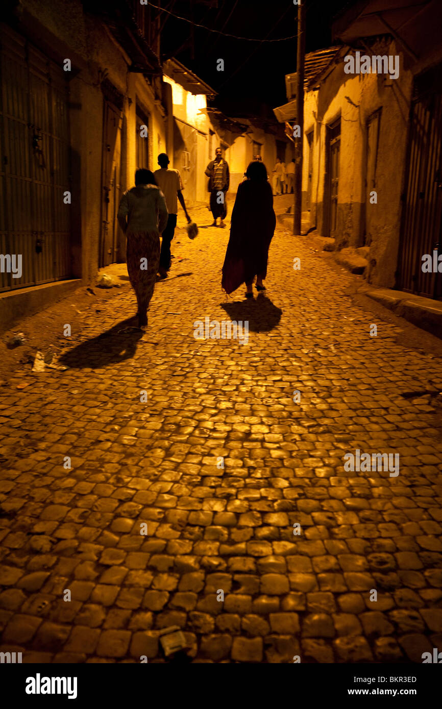 Ethiopia, Harar. Harari women cast long shadows under the streetlights. - Stock Image