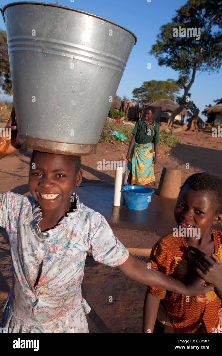 Malawi, Lilongwe, Ntchisi Forest Reserve. With a clean water supply villagers gather to collect water - Stock Image