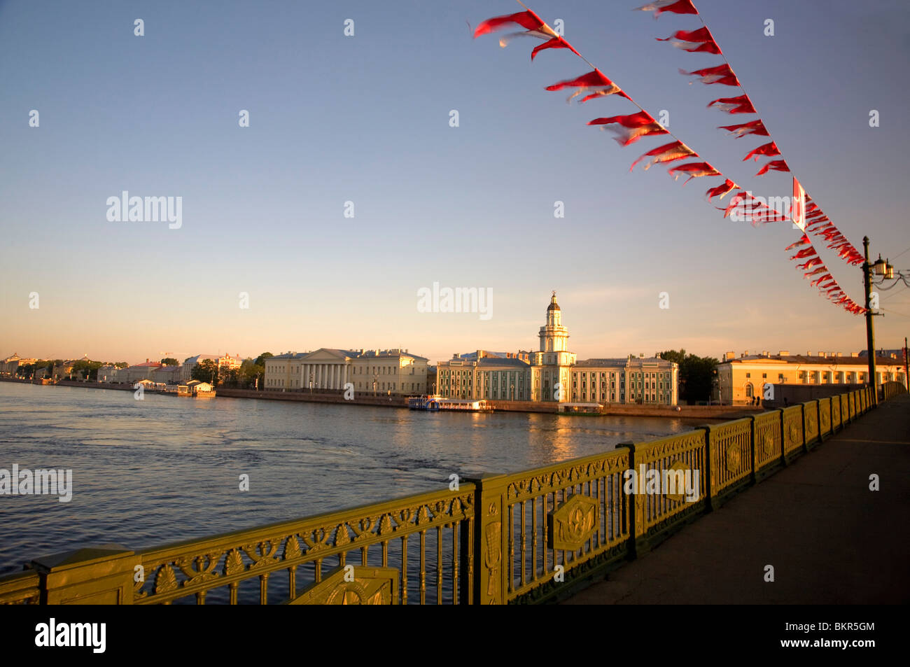 Russia, St.Petersburg; Across the Neva River early morning with the Kunskamera visible and flags in the foreground - Stock Image