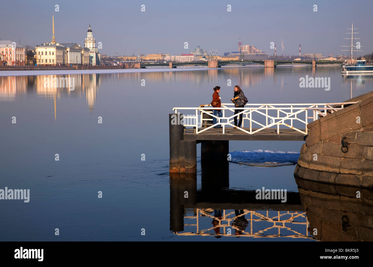 Russia, St.Petersburg; Two girls speaking on a bridge reflected on the Neva River with the Kunstkamera in the background - Stock Image