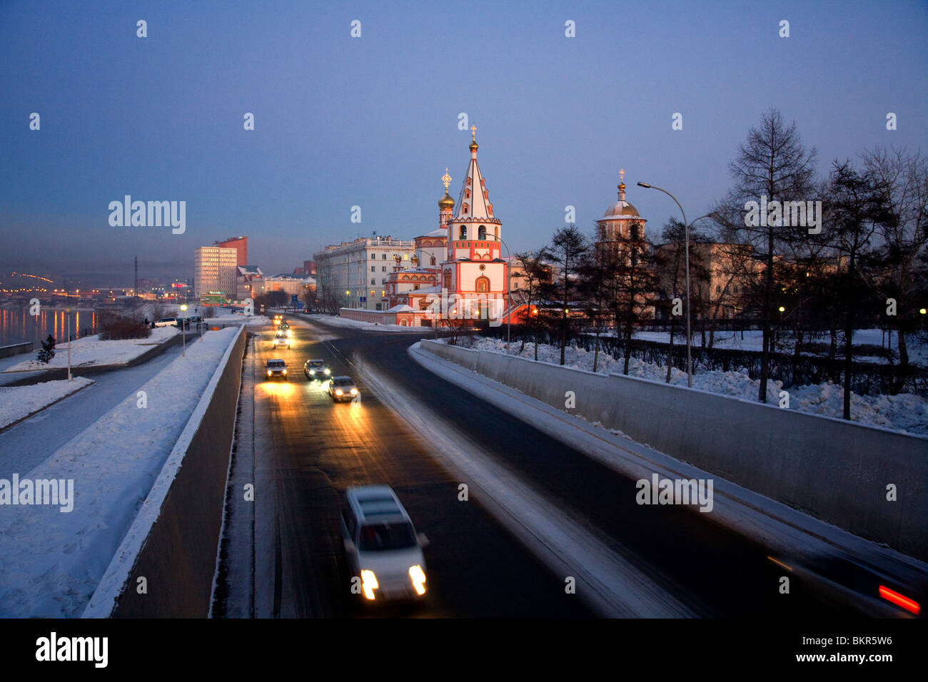 Russia, Siberia, Irkutsk; An Orthodox Church close to river Angara, and cars passing swiftly by. - Stock Image