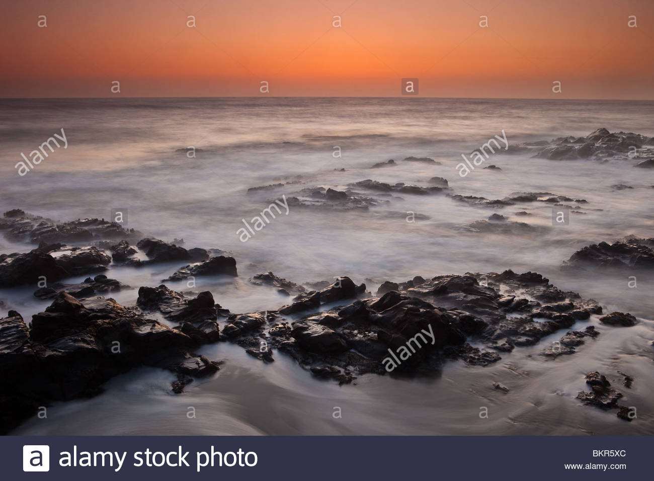 Colorful skies and twilight surf north of Santa Cruz on the Californian coast. - Stock Image