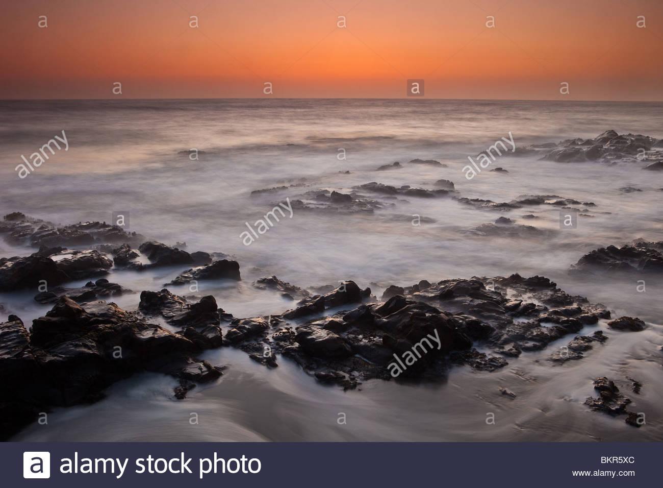 Colorful skies and twilight surf north of Santa Cruz on the Californian coast. Stock Photo