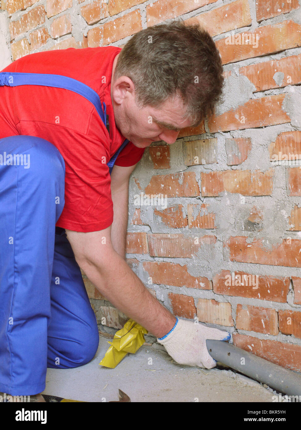 Plumber installing pvc sewage pipe inside unfinished house - Stock Image