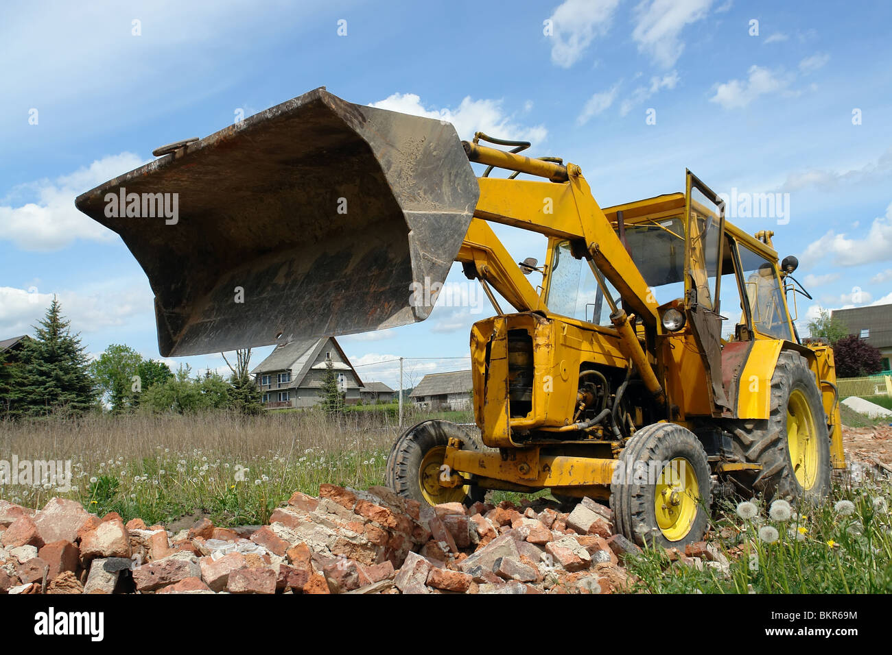 Yellow backhoe loader working with brick debris - Stock Image