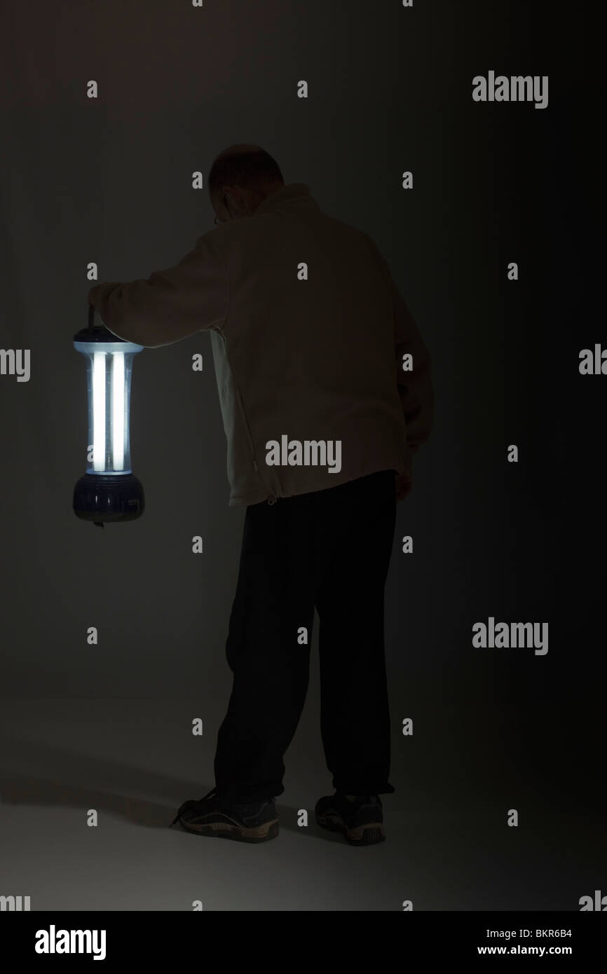 Man searching in darkness with portable light. Copy space. - Stock Image