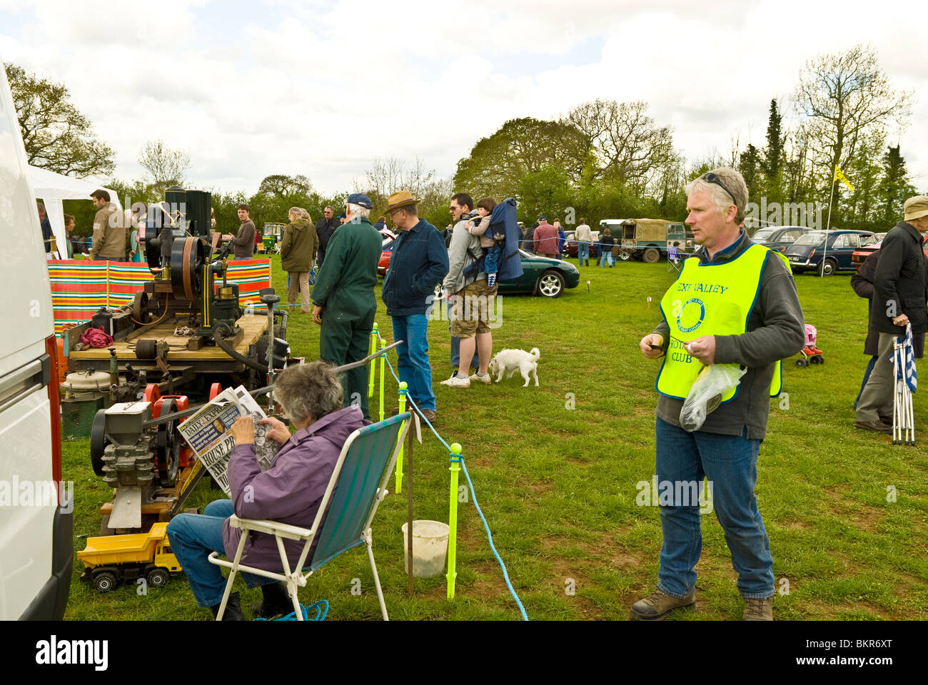County or country show with official approaching a lady in a deckchair reading a newspaper, Devon England UK 2010 - Stock Image