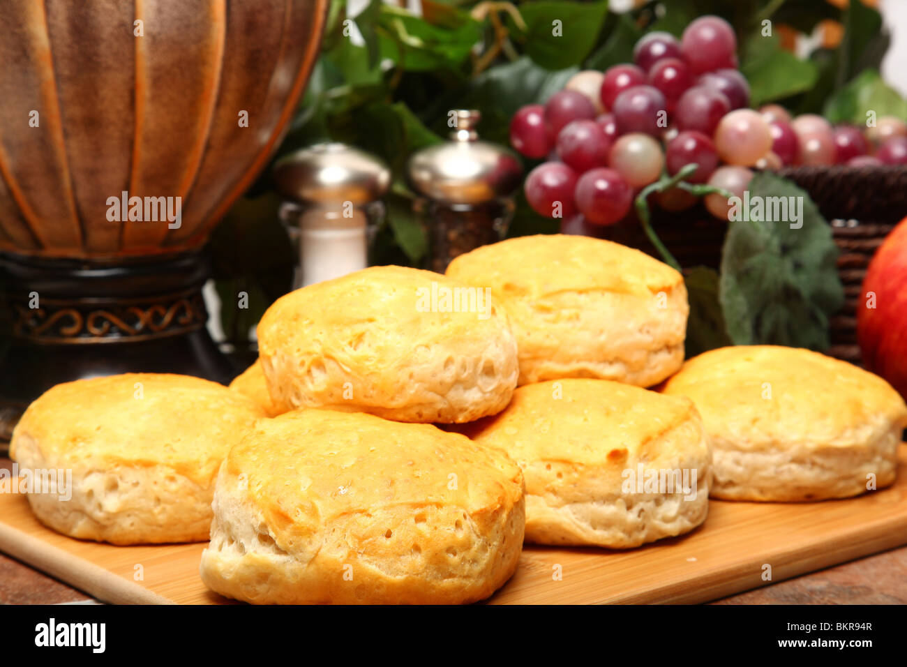 Stack of hot fresh breakfast biscuits on cutting board in kitchen. - Stock Image
