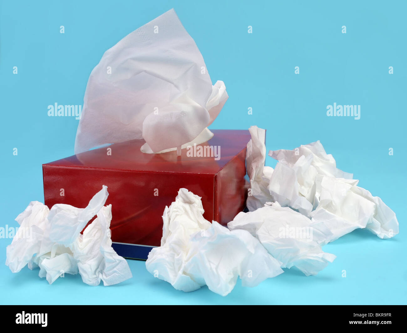 Paper tissue box with used tissues over light blue background - Stock Image
