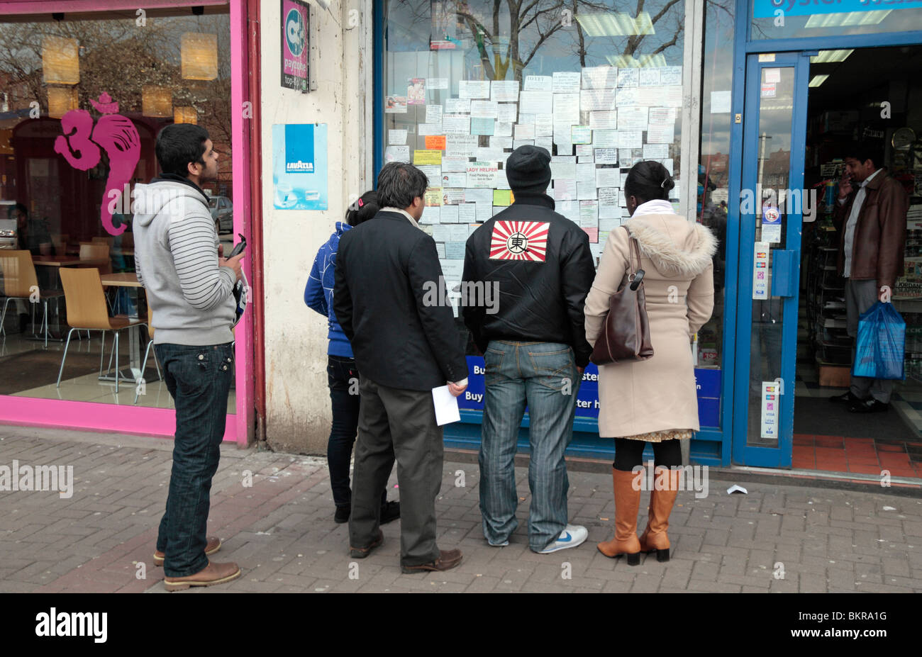 A group of people around a board full of small ads in a newsagent shop window in Hounslow West, Middx, UK. - Stock Image