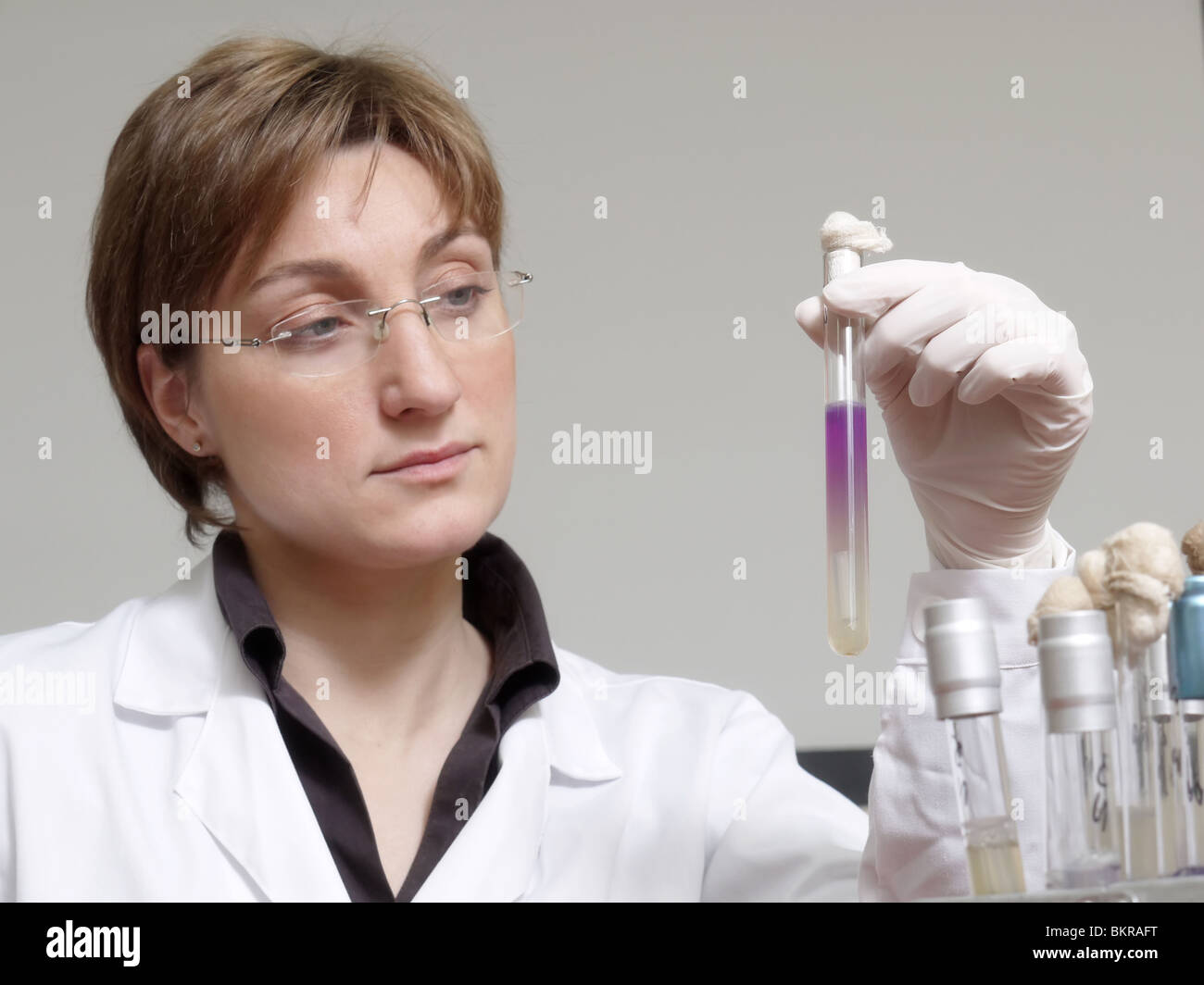 Female laboratory technician looking at test tube with specimen - Stock Image