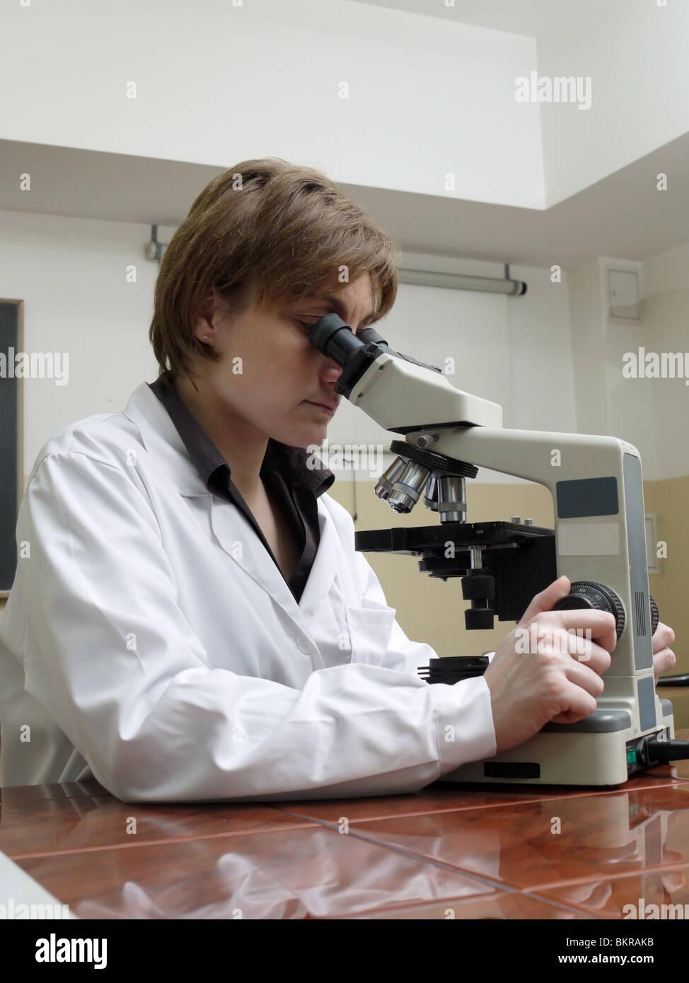 Female scientist analyzing specimen under the microscope - Stock Image