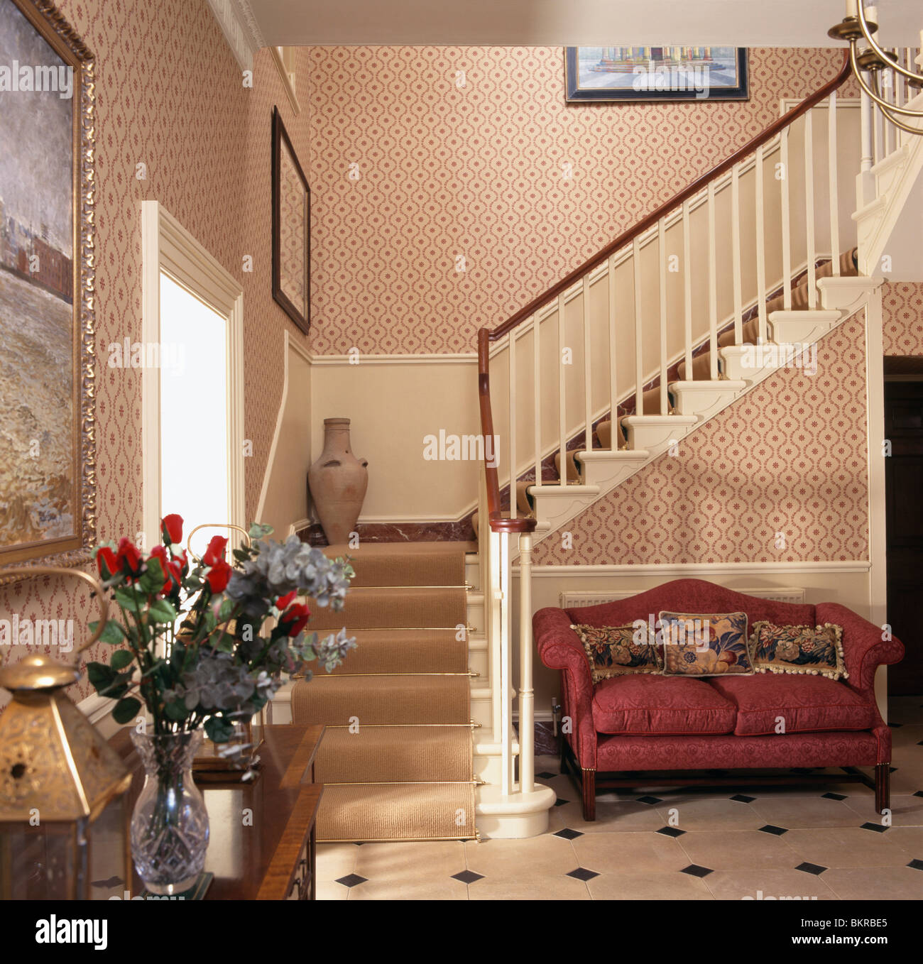 Red Sofa Below Staircase With Cream Carpet In Traditional Cream Hall