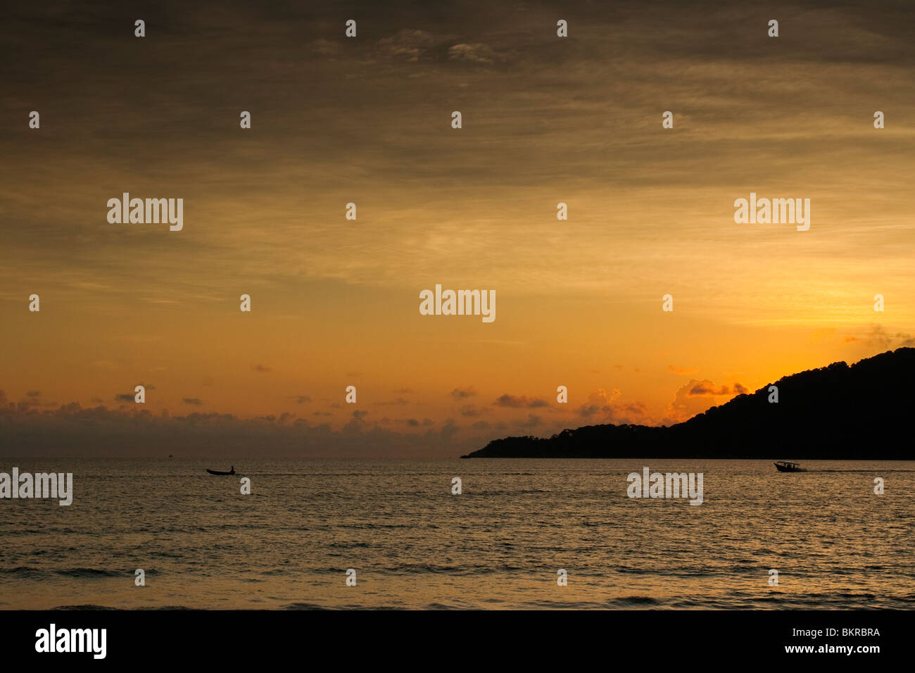 Dawn over the South China sea and the island of Pehentian Besar, seen from Long Beach in Perhentian Kecil. - Stock Image