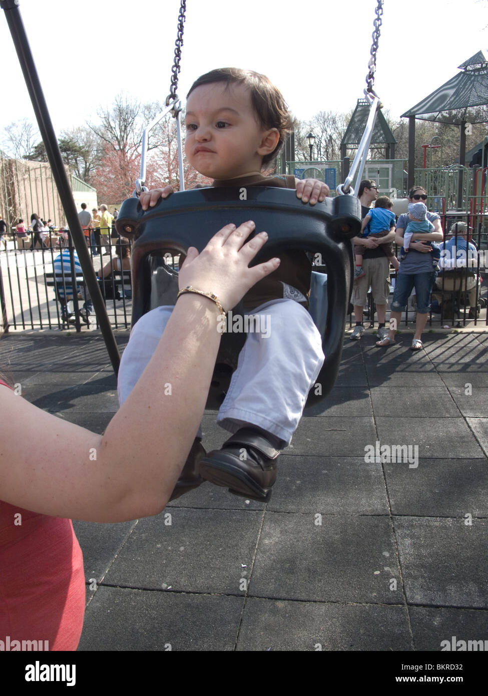 One year old boy on the swings with mom in Prospect Park, Brooklyn, NY - Stock Image