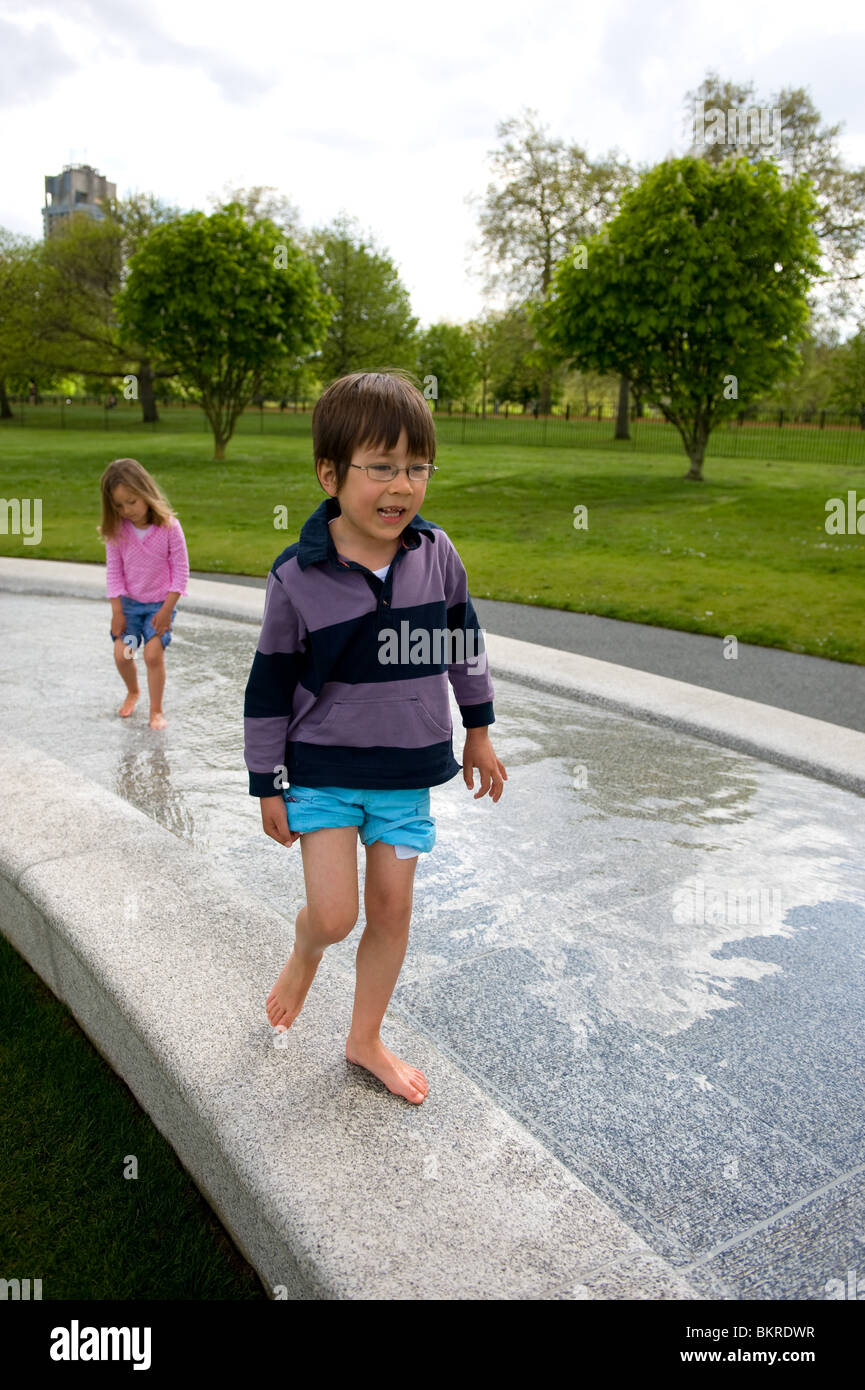 Two children playing in the Princess Diana memorial fountain in Hyde Park, London. - Stock Image