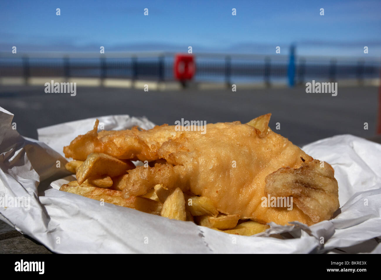 traditional english fish and chips in paper wrapper on a pier at the seaside england uk - Stock Image