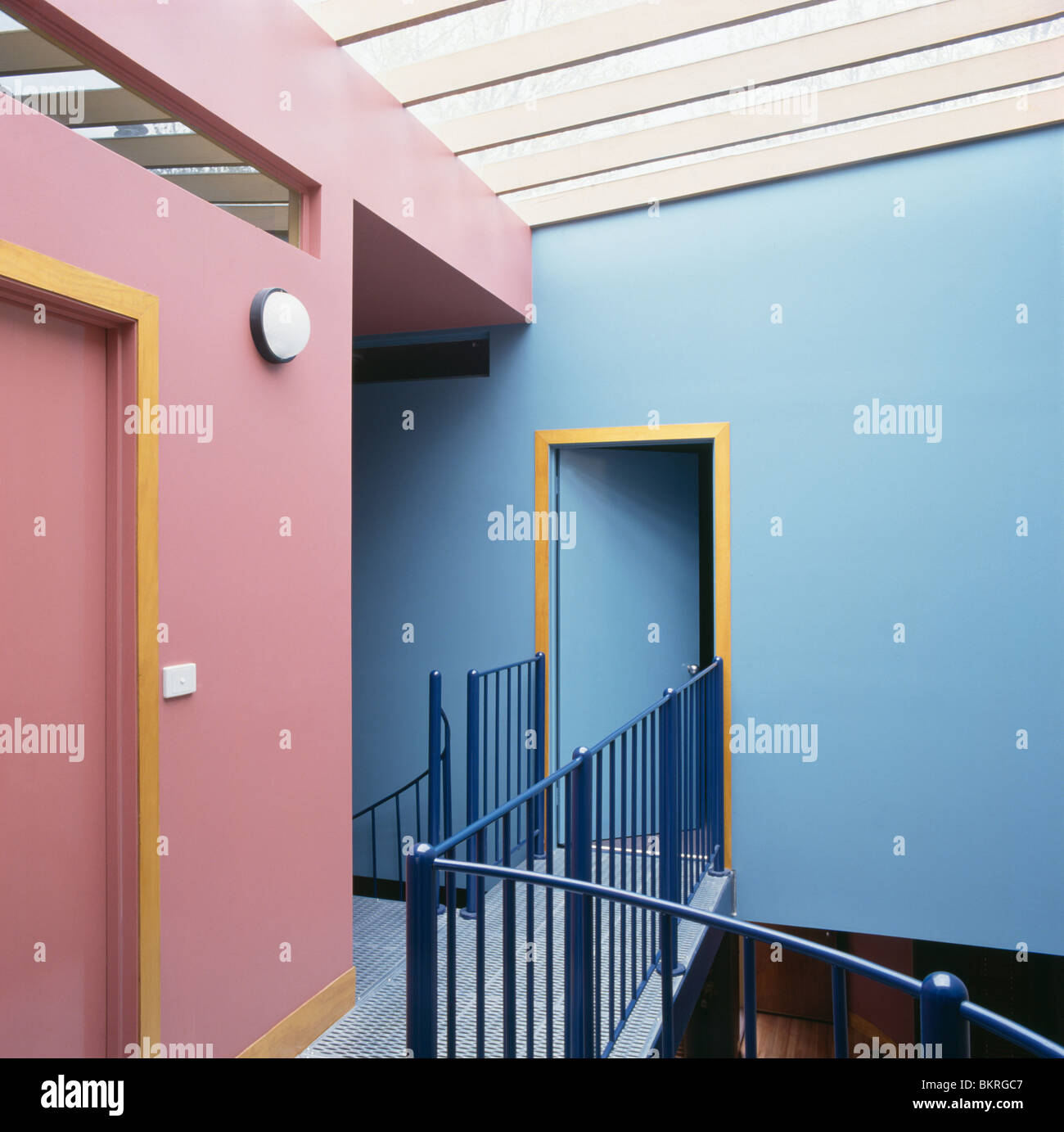 Modern pink and blue landing with metal banisters Stock Photo