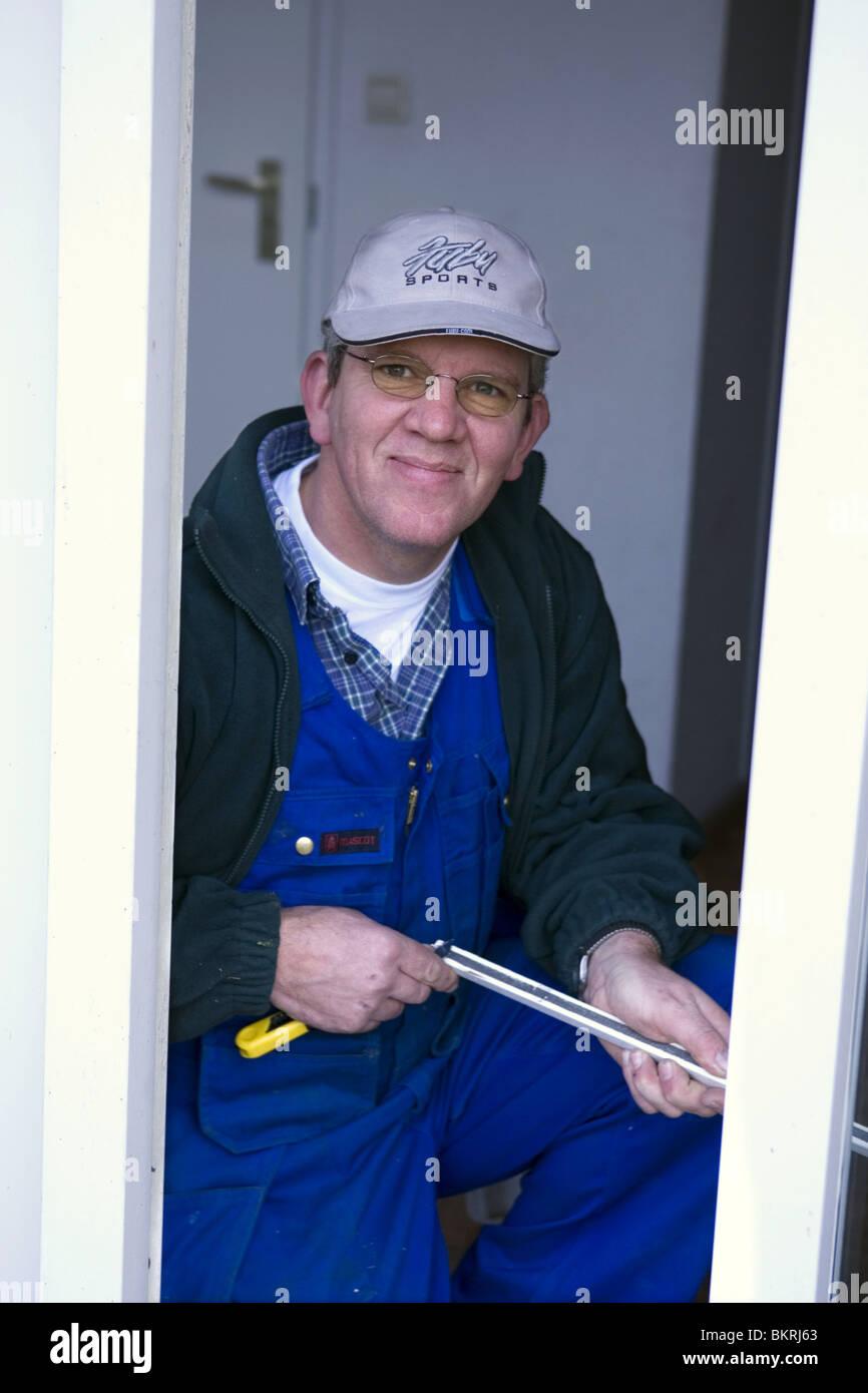 Craftman repairing door - Stock Image